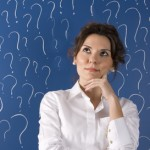 thinking business woman in front of question marks