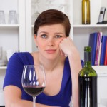 Woman with blue shirt short pixie cute brunett hair drinking red wine looking board 166314390